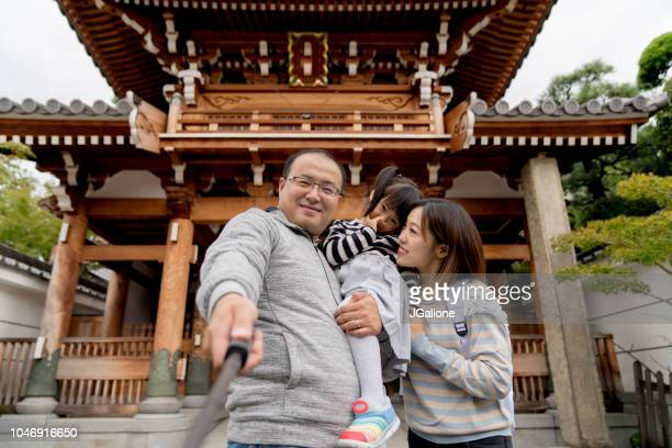 Family of tourists taking a selfie at a Japanese Temple