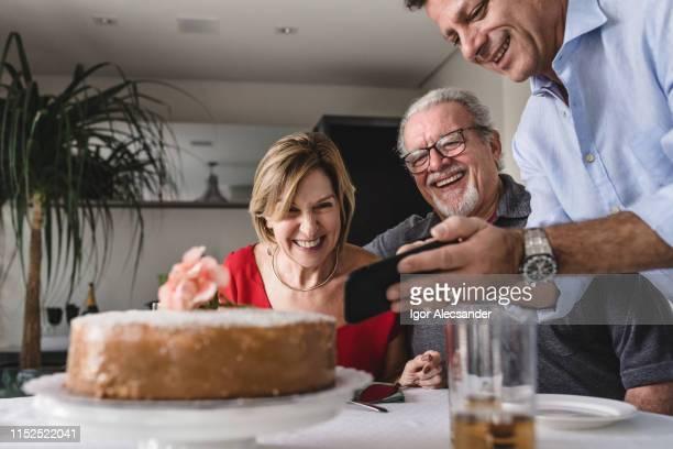 familia de dos generaciones viendo imágenes en el teléfono inteligente - aniversario fotografías e imágenes de stock