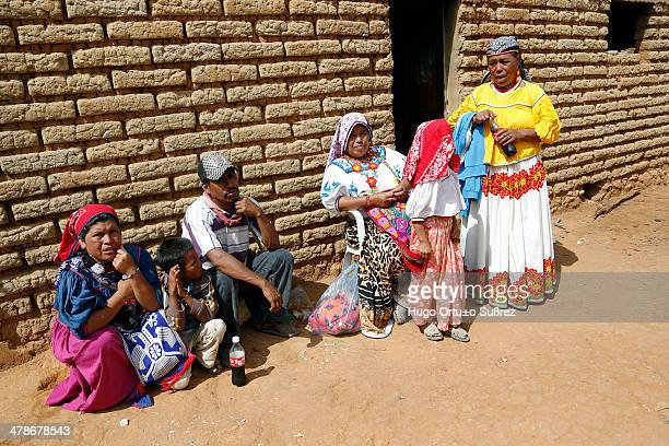 Family of wixaricas is recharged on an adobe house on a sunny day in Mezquitic. The ethnic Wixarika have large populations in the states of Jalisco,...
