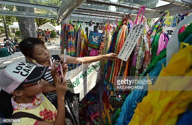 A family offers colorful paper cranes in honour of the victims of the 1945 atomic bombing at the Peace Memorial Park in Hiroshima on August 5 2015...