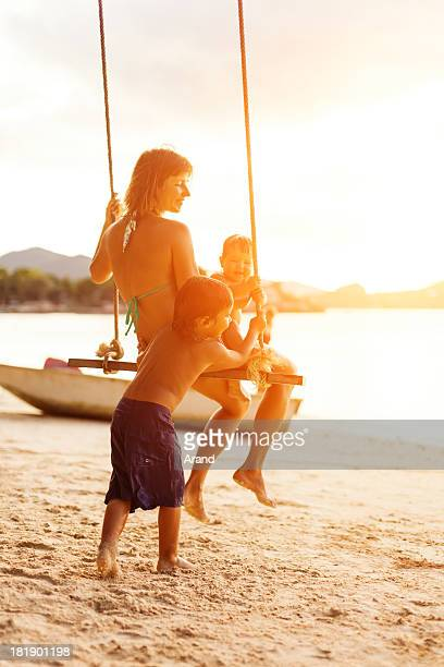 Family on a beach rope swing.
