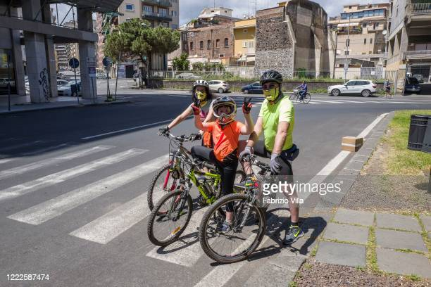 A family on a bike ride wearing protective masks on this first Sunday in May the last day of lockdown in Italy on May 03 2020 in Catania Italy Italy...
