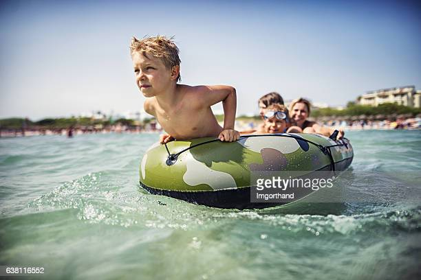Family on a boat playing and having fun at sea