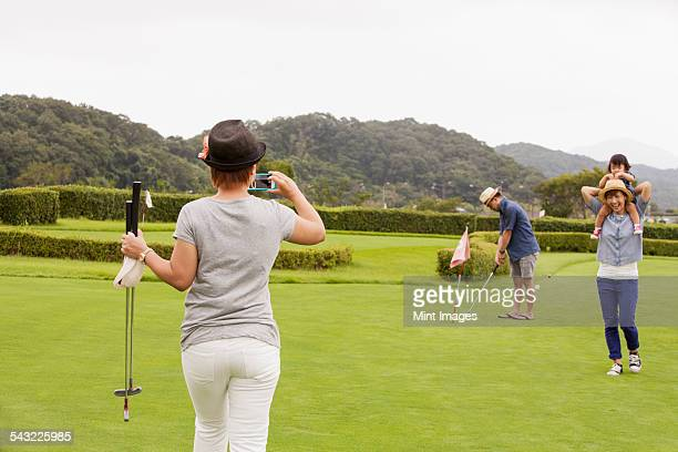 Family on a golf course. A child and three adults. a woman with a camera.