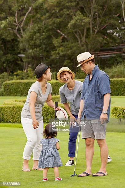 family on a golf course. a child and three adults. - 麦わら帽子 ストックフォトと画像