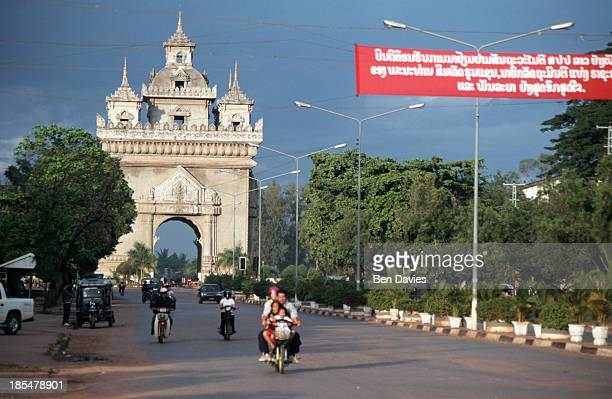 A family on a motorbike drives in front of the Patuxai a gigantic concrete monument in the centre of Vientiane reminiscent of the Arc de Triomphe in...
