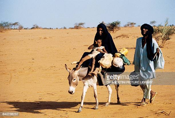Family on a path in the Sahel desert area Mali