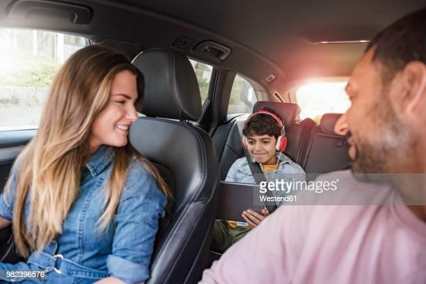 family on a road trip with boy using tablet - family inside car - fotografias e filmes do acervo