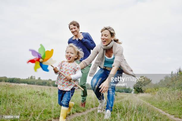 family on a trip with daughter holding pinwheel - activiteit bewegen stockfoto's en -beelden