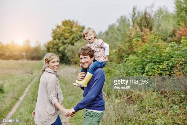 family on a trip with father carrying daughter on shoulders - family with one child stock pictures, royalty-free photos & images
