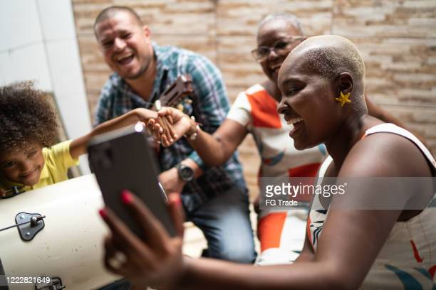 family on a video chat while playing music at home - video chat - samba stock pictures, royalty-free photos & images