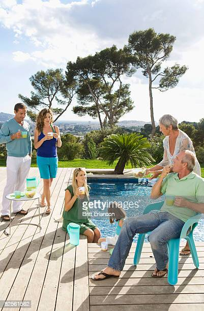 family on a wooden terrace by a pool - bouches du rhone stock pictures, royalty-free photos & images