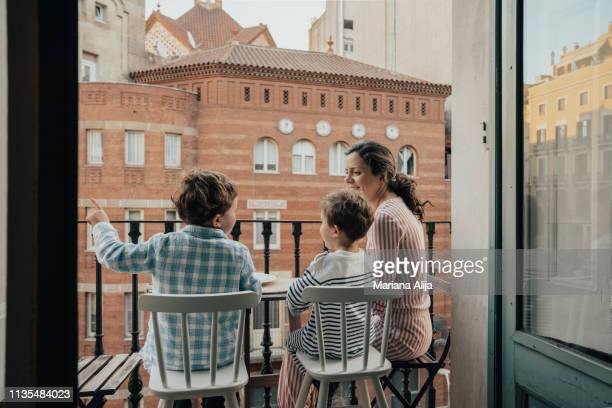 family on balcony - apartment balcony stock pictures, royalty-free photos & images