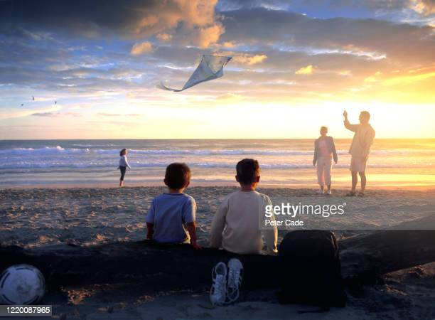 family on beach at sunset - vacations stock pictures, royalty-free photos & images