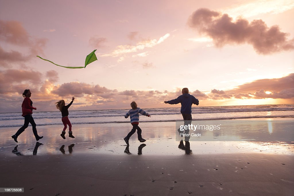 Family on beach at sunset with kite : Stock Photo