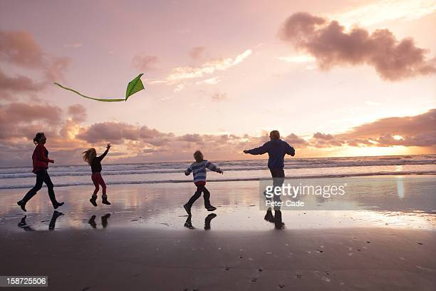 Family on beach at sunset with kite