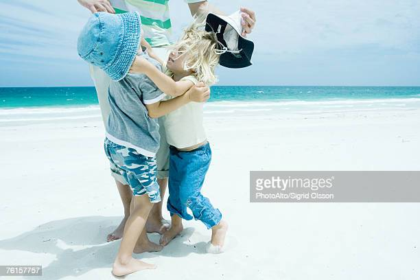 'Family on beach, boy and girl reaching for each other in front of father'