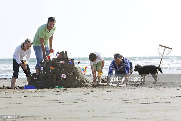 family on beach building large sandcastle - cornish flag stock pictures, royalty-free photos & images