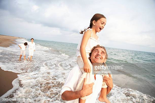 Family on beach, daughter (6-8) sitting on father's shoulders, smiling