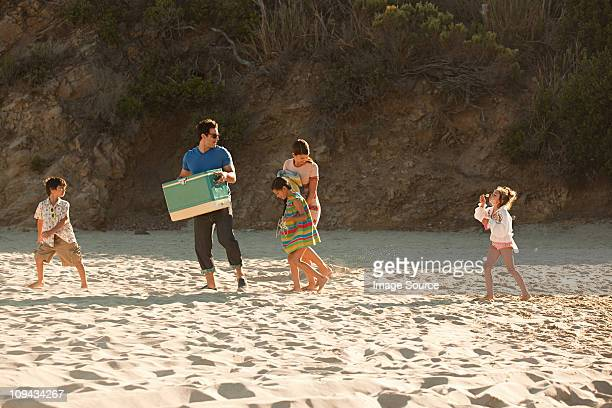 Family on beach, father carrying coolbox