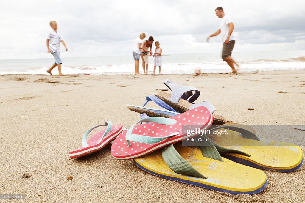 Family on beach, flip-flops in foreground : Stock Photo