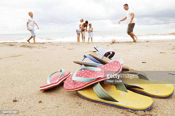 family on beach, flip-flops in foreground - flip flop stock pictures, royalty-free photos & images
