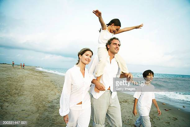 Family on beach, girl (6-8) on father's shoulders, arms outstretched
