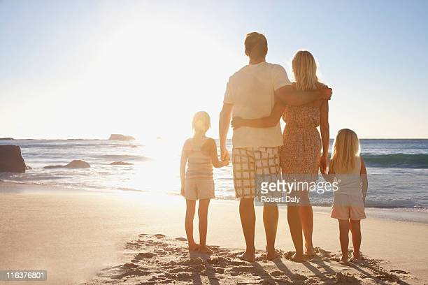 Family on beach holding hands