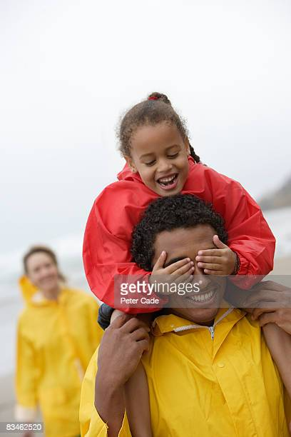 family on beach in bad weather - piggyback stock pictures, royalty-free photos & images