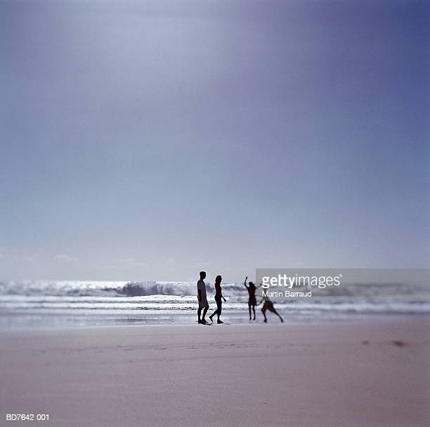 family on beach in surf - mid distance stock pictures, royalty-free photos & images
