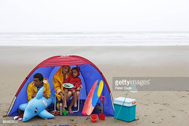 Family on beach in the rain