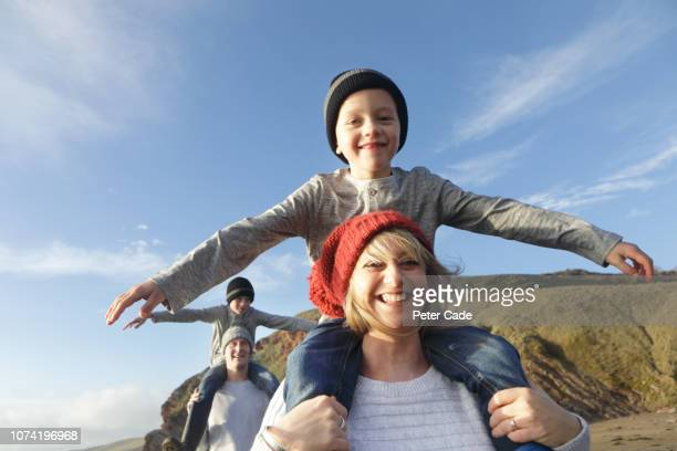 family on beach in winter, mother giving son piggyback - beauty in nature stock pictures, royalty-free photos & images