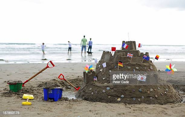 family on beach, large sandcastle with flags - cornish flag stock pictures, royalty-free photos & images