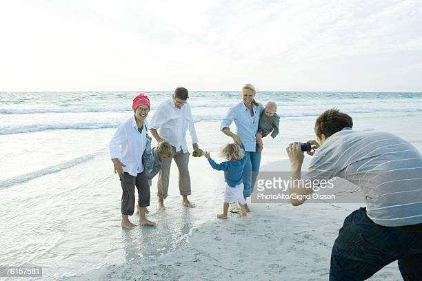'Family on beach, man taking photo'