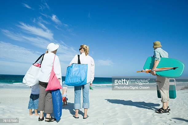family on beach - woman carrying tote bag stock photos and pictures