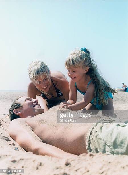 family on beach - burying stock pictures, royalty-free photos & images