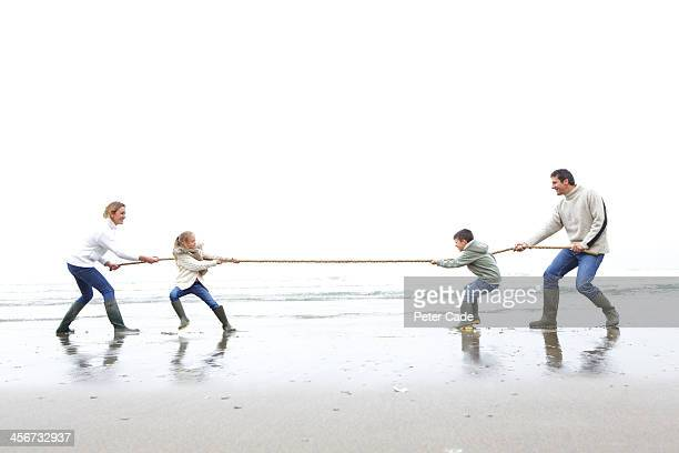 Family on beach playing tug of war