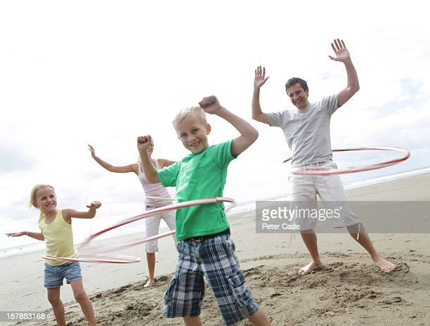 Family on beach playing with hula-hoops