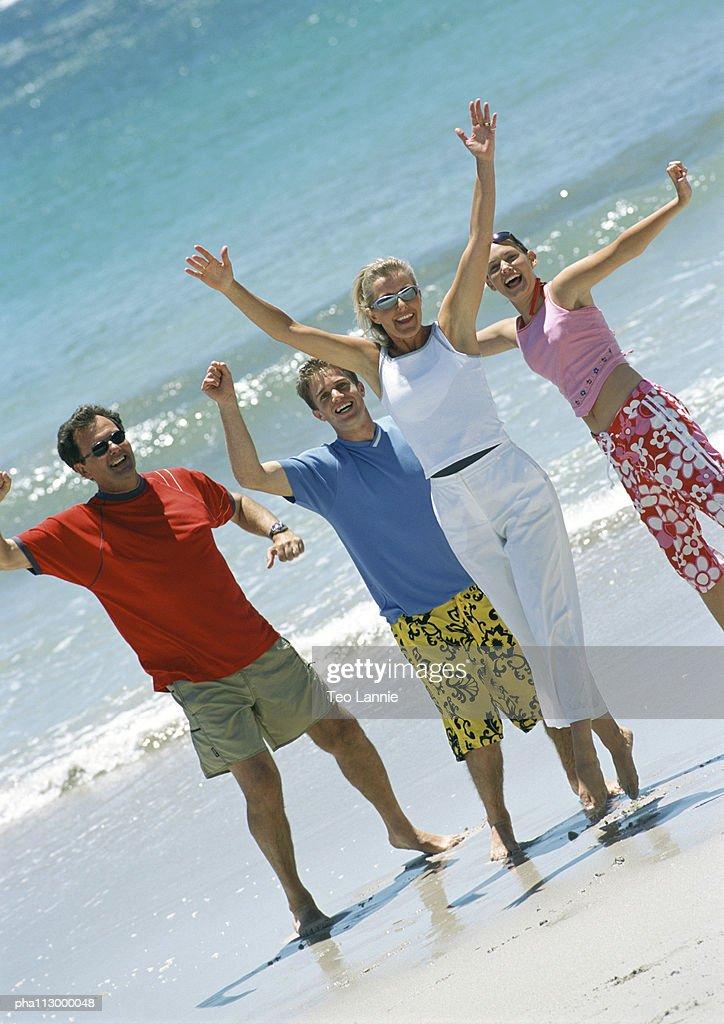 Family on beach, waving : Stockfoto