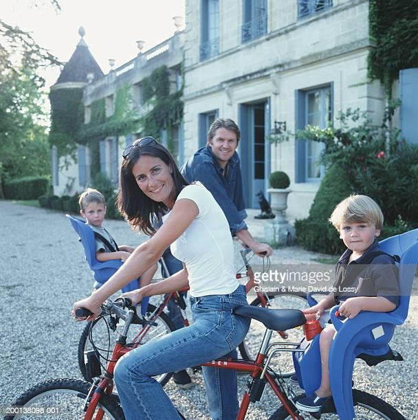 Family on bikes, smiling, portrait