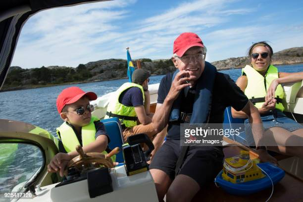 family on boat - life jacket stock pictures, royalty-free photos & images