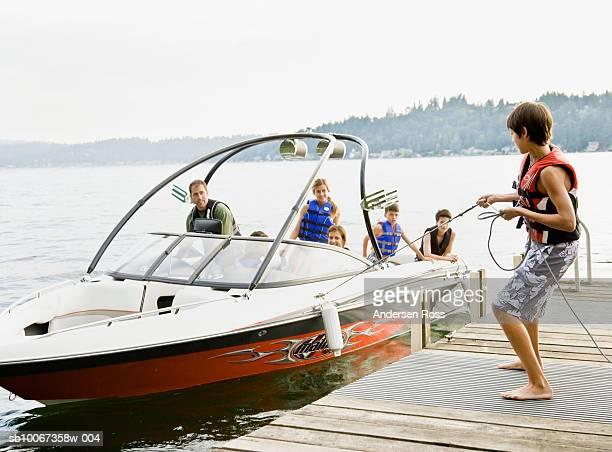 Family on boat, teenage boy holding rope