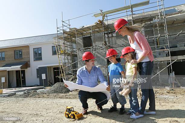 Family on building site looking at house plans