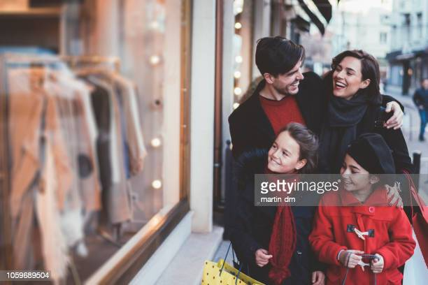 family on christmas shopping - black friday stock photos and pictures