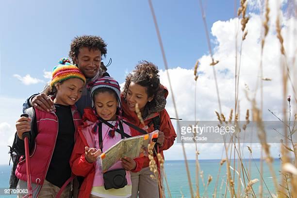 family on coastal path reading map