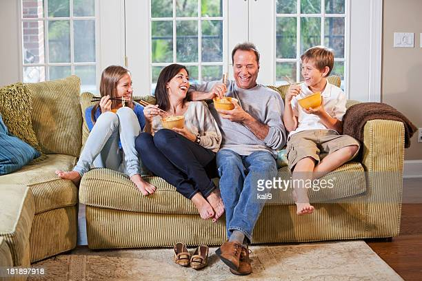 Family on couch, eating, talking