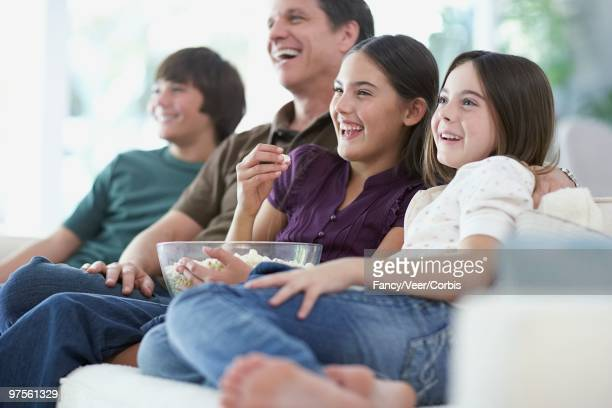 family on couch watching television - vestido roxo - fotografias e filmes do acervo
