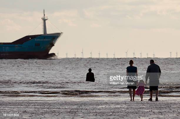 CONTENT] Family on Crosby beach with Anthony Gormley ironman statue from 'Another place' in the river mersey / Irish sea with windturbines and a ship...