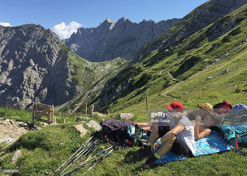 A family on day three of a four-day, 50km hike across the Karwendel mountain range take a break as their destination for the day, the Lammsenjochhuette hikers' and climbers' hut, stands behind in the center of the image on August 9, 2015 near Engalm, Austria. The Karwendel mountain range, part of the Austrian Alps, is located in central Tyrol and is a popular summer destination for mountain bikers, climbers and hikers. Mountain huts operated by alpine clubs and scattered across the region offer food and shelter.