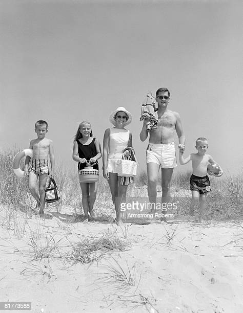 Family on five, in bathing suits, walking towards beach, carrying parasol and picnic.